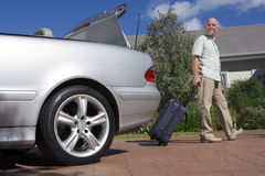 Senior man pulling suitcase on wheels from parked car boot on driveway, smiling, side view, portrait (surface level) royalty free stock images