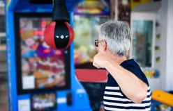 Senior man punching the boxer arcade. At carnival Royalty Free Stock Photography