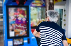 Senior man punching the boxer arcade. At carnival Stock Photography