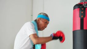 Senior man punching a boxing sack stock video footage