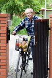 Senior man pushing bike through the gate Stock Photos