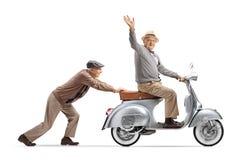 Senior man pushing a senior gentleman riding a vintage scooter and waving at the camera royalty free stock photography