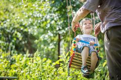 Senior man pushing happy grandson on swing Stock Photo