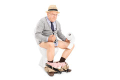 Senior man pushing hard seated on a toilet Royalty Free Stock Photography