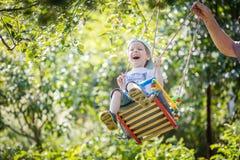 Senior man pushing laughing grandson on swing. In garden Royalty Free Stock Images