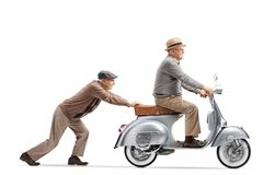 Senior man pushing a senior gentleman riding a vintage scooter stock photo