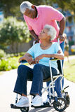 Senior Man Pushing Wife In Wheelchair Stock Images