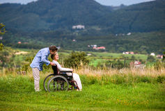 Senior man pushing woman in wheelchair, green autumn nature Stock Photos