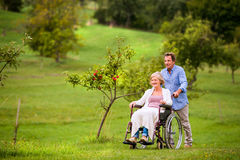 Senior man pushing woman in wheelchair, green autumn nature Stock Images