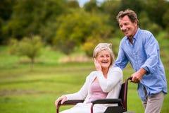 Senior man pushing woman in wheelchair, green autumn nature Royalty Free Stock Photography