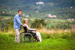 Senior man pushing woman in wheelchair, green autumn nature Royalty Free Stock Image