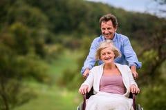 Senior man pushing woman in wheelchair, green autumn nature Royalty Free Stock Photo