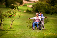Senior man pushing woman in wheelchair, green autumn nature. Senior men pushing women sitting in wheelchair oustide in green autumn nature, laughing, arms Stock Photo