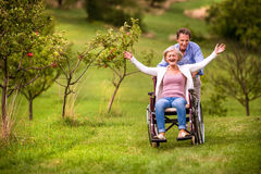 Senior man pushing woman in wheelchair, green autumn nature. Senior men pushing women sitting in wheelchair oustide in green autumn nature, laughing, arms Royalty Free Stock Image