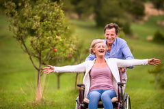 Senior man pushing woman in wheelchair, green autumn nature. Senior men pushing women sitting in wheelchair oustide in green autumn nature, laughing, arms Royalty Free Stock Photo