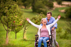 Senior man pushing woman in wheelchair, green autumn nature. Senior men pushing women sitting in wheelchair oustide in green autumn nature, laughing, arms Stock Photos