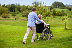Senior man pushing woman in wheelchair, green autumn nature Stock Photography
