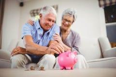 Senior man putting coins in piggy bank Stock Image