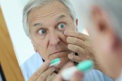 Senior man putting contact lenses in his eyes Royalty Free Stock Photos