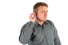 Senior man putting on a hearing aid. Studio shot isolated on whi Stock Images