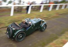 Senior man racing vintage car on hill climb track.