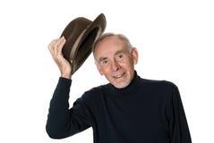 Senior man raising his hat. Smiling senior raising his hat in polite greeting Royalty Free Stock Images