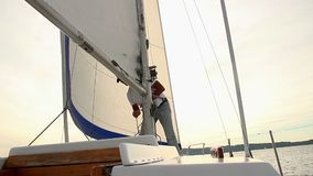 Senior man raising the mainsail on boat, yachting, traveling. Stock footage stock video footage