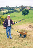 Senior man raking hay with pitchfork on field Stock Photos