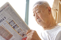 A senior man is reading. Newspaper Stock Photos
