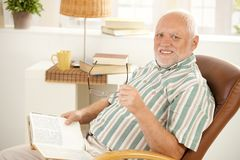 Senior man reading in armchair. Senior man reading book in armchair at home, holding glasses, looking at camera, smiling Stock Photography