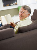 Senior man reading book. At home and looking over shoulders Stock Photography