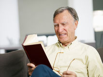 Senior man reading book. At home. Copy space Royalty Free Stock Photography