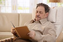 Senior man reading book. Senior man resting in chair at home, reading book Royalty Free Stock Photo