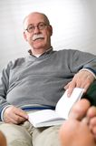 Senior man reading book. While sitting on couch Stock Image