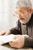 Senior man reading book. Senior gray-haired man reading book indoors Royalty Free Stock Image