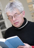 Senior man reading book. A senior grey haired man wearing glasses, reading a book Stock Images
