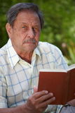 Senior man reading book. Healthy looking senior man is his late 70s sitting in garden at home and reading book, outdoor Royalty Free Stock Images