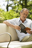 Senior Man Reading Book In Backyard Stock Photos