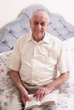 Senior Man Reading Book On Bed. Smiling at camera Royalty Free Stock Photography