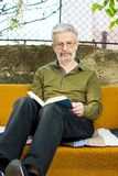 Senior man reading a book in the backyard. Senior man reading a book on a bed in the backyard Royalty Free Stock Image