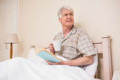 Senior man reading a book in bed Royalty Free Stock Images