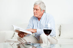 Senior man reading book on couch Stock Photos