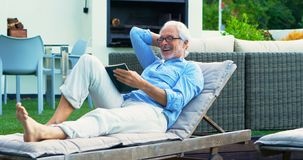 Senior man reading a book in garden 4k stock video footage