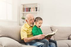 Senior man reading book for his grandchild. Senior men reading book for his grandchild. Cheerful grandfather telling fairy tale aloud to his excited grandson Stock Photos