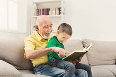 Senior man reading book for his grandchild. Senior men reading book for his grandchild. Cheerful grandfather telling fairy tale aloud to his excited grandson Stock Image