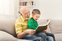 Senior man reading book for his grandchild. Senior men reading book for his grandchild. Cheerful grandfather telling fairy tale aloud to his excited grandson Royalty Free Stock Photos