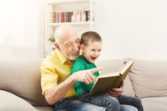 Senior man reading book for his grandchild. Senior men reading book for his grandchild. Cheerful grandfather telling fairy tale aloud to his excited grandson Stock Photography