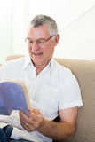 Senior man reading book at home Stock Images
