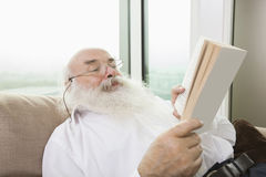 Senior man reading book in house Royalty Free Stock Image