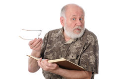 Senior man reading a book, isolated on white. Handsome bald and bearded senior man distracted when reading a book, isolated on white background Stock Photo